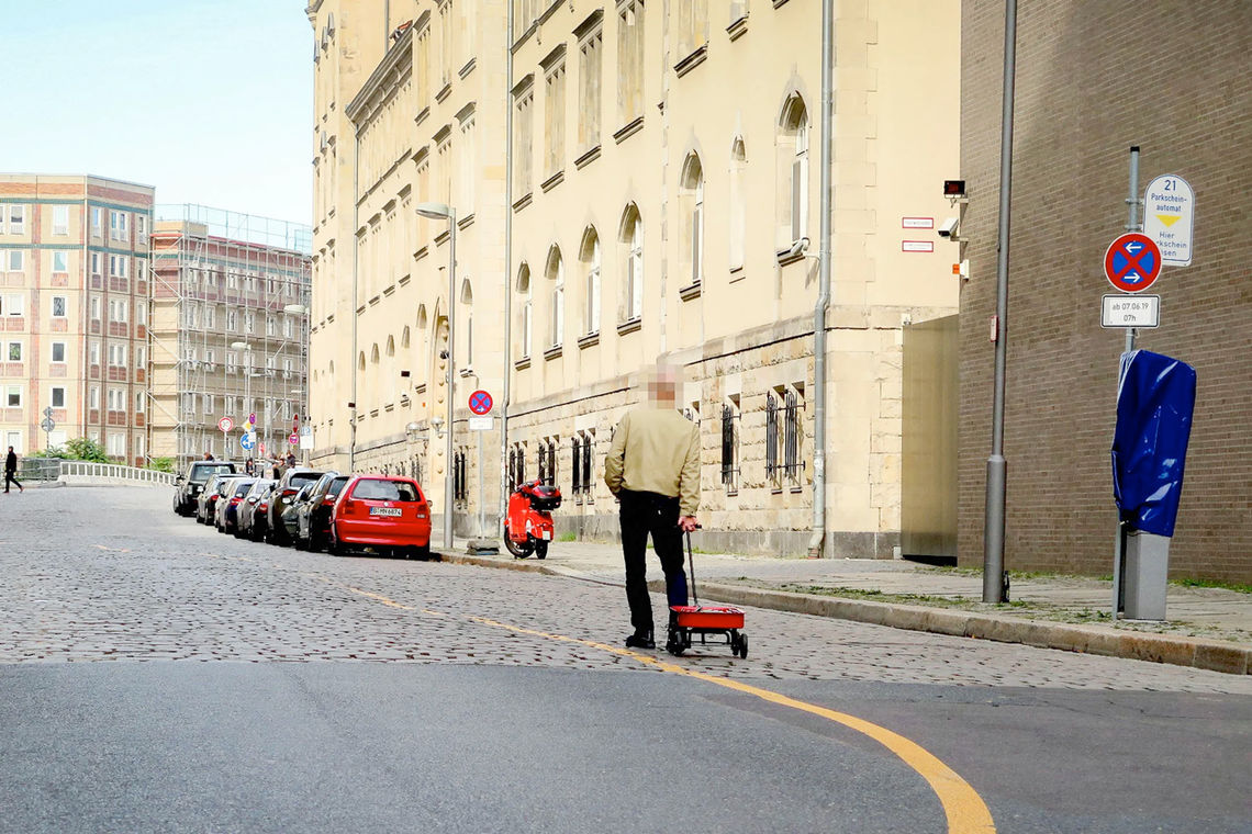 Weckert carrying a red cart full of smartphones in Berlin