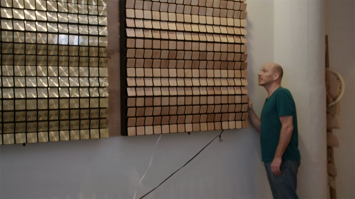 "Daniel Rozin inspecting his mirror installations. Screen capture from Wired's ""How This Guy Makes Amazing Mechanical Mirrors"", 2019"